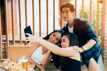Asian friends smiling and taking selfie in restaurant.