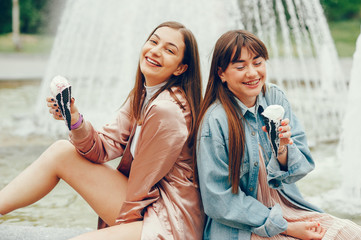 Two girls sitting near the fountain and going ice cream.