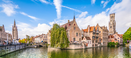 Wall Murals Bridges Panoramic city view with historical houses, church, Belfry tower and famous canal in Bruges, Belgium.