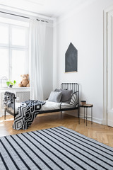 Striped carpet in white bedroom interior with patterned blanket on bed near window. Real photo