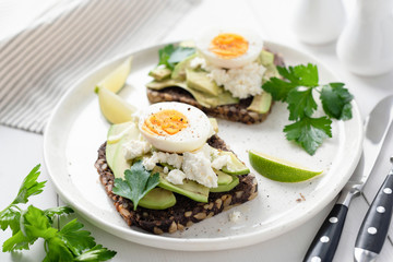 Whole grain toast with avocado, egg, white cheese. Closeup view
