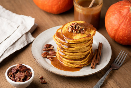 Homemade pumpkin pancakes with cinnamon, caramel and nuts on rustic wooden table
