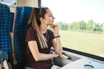 Young beautiful girl tourist travels by train. She looks out the window while the train is moving.