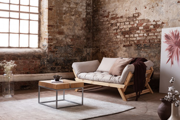 Wooden table on carpet next to grey settee in wabi sabi living room interior with poster and...