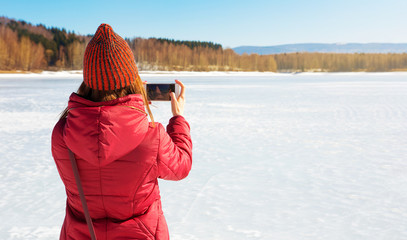 Girl taking picture of a frozen lake with phone