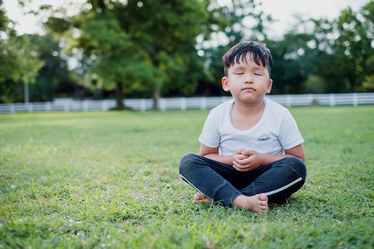 Asian little boy meditation with peace and relax in the park outdoor.Meditation concept with copy space.