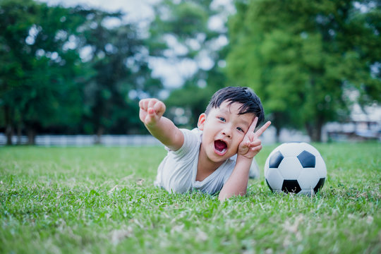 Little Asian child playing football and celebrating on grass.