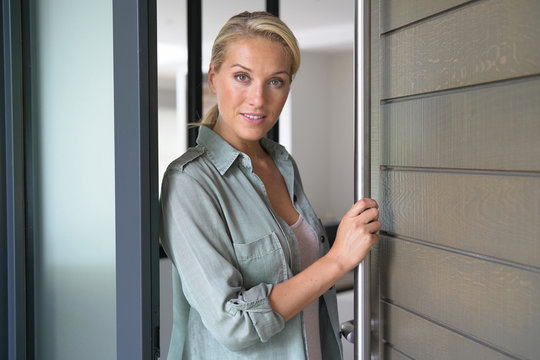 Blond woman welcoming people at entrance front door