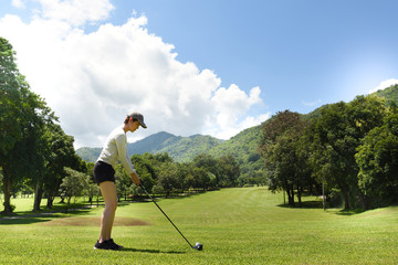 Young Asian woman playing golf on a beautiful natural golf course