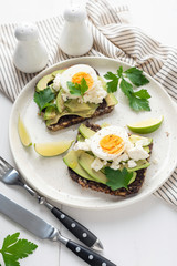 Wholegrain toast with avocado, egg and soft cheese on white plate, healthy breakfast healthy eating concept