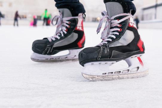 Man's hockey skates on ice background