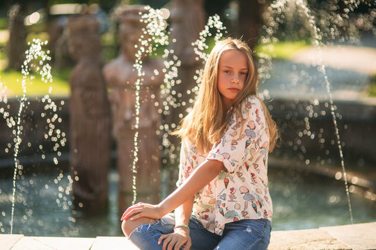 blond teenage girl in a blond blouse playing with her hair on the background of a fountain
