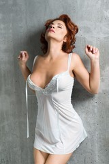 Attractive redhead adult woman in lingerie with eyes closed stands near a gray concrete wall