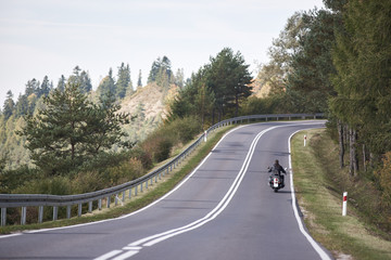 Back view of motorcyclist in black leather outfit with long hair riding cruiser motorbike up twisted empty asphalt road on bright sunny summer day by green forest trees under clear blue cloudless sky.