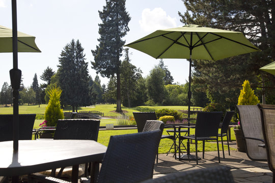Sunlit patio with table, chairs and umbrella with view of golf course greens