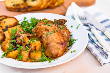 Healthy rustic food - stew chicken with potatoes in tomato sauce on a white plate, close-up