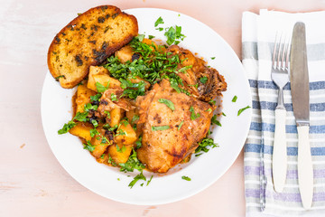 Italian food - stewed chicken with potatoes in tomato sauce on a plate and toasted bread, close-up