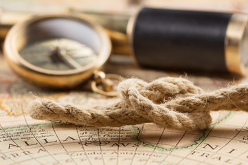 antique compass, spyglass on old map with rope