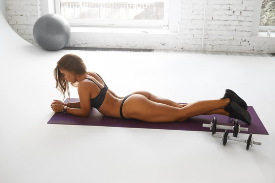 Indoor shot of gorgeous sexy female with tanned muscular body lying on her stomach wearing lingerie and sneakers, lifting feet for toned strong butt muscles. Athletic woman training on mat