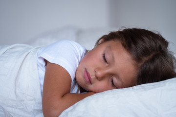 Portrait of a young girl (kid) sleeping on the bed. Concept: Relax, family