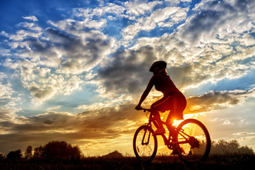 Silhouette of girl riding bicycle on background of setting sun