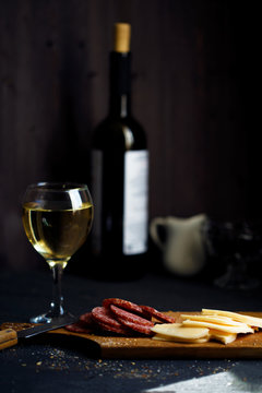Charcuterie, cheese, salami and a glass of wine on a dark table