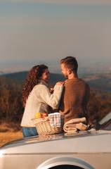 Beautiful young couple enjoying picnic time on the sunset.