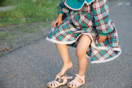 Little girl legs wearing open-toe sandals at summer. Child in green dress