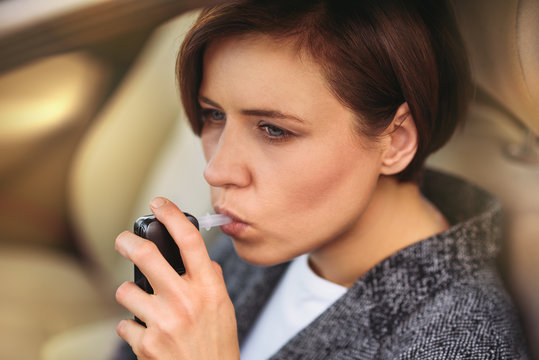 Young millennial woman using breath alcohol analyzer in the car. Closeup with selective focus. Girl taking alcohol test with breathalyzer.