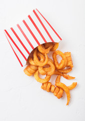 Curly fries fast food snack in paper container on stone kitchen background. Unhealthy junk food