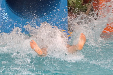 Young girl fun rolls down a hill in the water park
