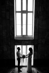 Black and white picture of bride and groom standing before tall bright window