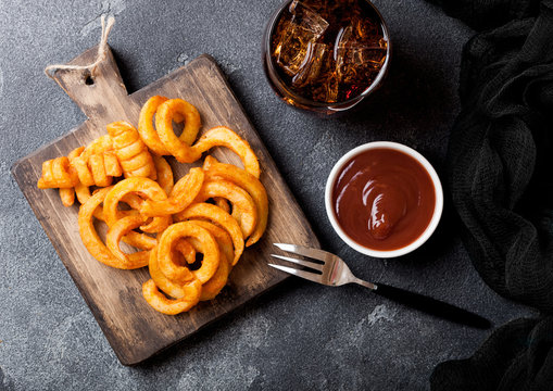 Curly fries fast food snack on wooden board with ketchup and glass of cola on stone kitchen background. Unhealthy junk food