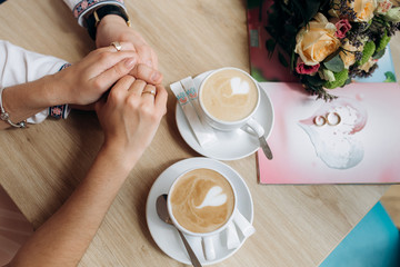 Man and woman hold each other hands on a table with two cups of coffee