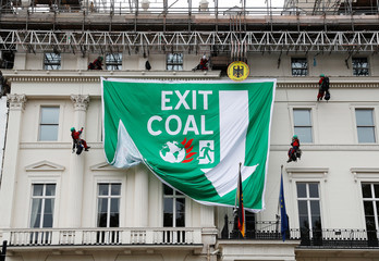 Greenpeace activists abseil down the facade of Germany's embassy as they unfurl a banner against coal, in London