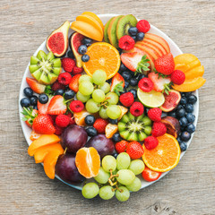 Wall Mural - Healthy fruit platter, strawberries raspberries oranges plums apples kiwis grapes blueberries on the dark grey wooden table, top view, copy space for text, square, selective focus