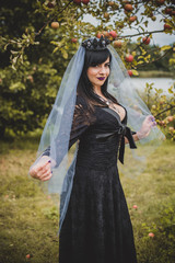Halloween party concept, mysterious girl in  handmade dress vintage style. Beautiful young dark witch woman. Inspiration for halloween celebration, ideas and simple nice detail