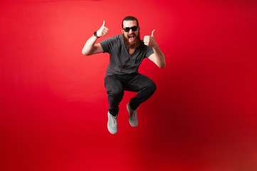 Cheerful bearded hipster man with sunglasses jump over red background and showing thumbs up