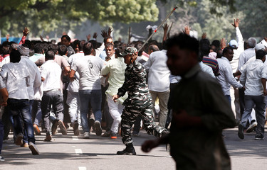 Police officer uses baton to disperse sanitation workers during protest in New Delhi