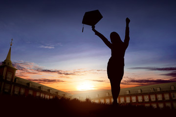 Silhouette of excited woman with graduation hat celebrating graduation