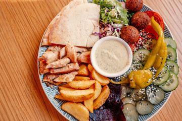 Traditional falafel balls with salad and hummus on a plate top view with copyspace