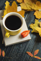 Yellow coffee mug and book on a dark wooden table with autumn scarf and leaves