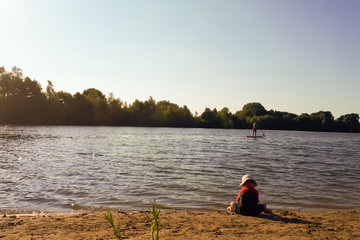 A young boy in a hat sits on the beach and plays with the sand next to the lake. An adult man is swimming on the lake.