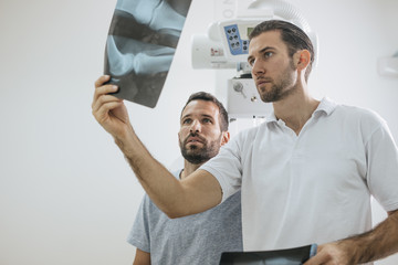 Doctor and His Patient Examining X-ray Films