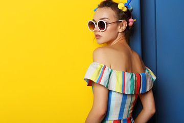 Fashion cool girl posing in sunglasses on yellow background.