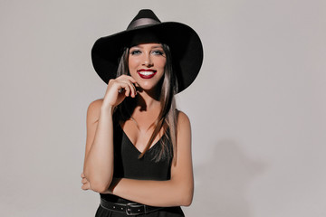 Happy smiling elegant woman with bright make up wearing black dress and hat  with great smile standing with arms folded and looking at camera isolated over white background