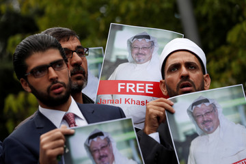 Human rights activists and friends of Saudi journalist Khashoggi hold his pictures during a protest outside the Saudi Consulate in Istanbul