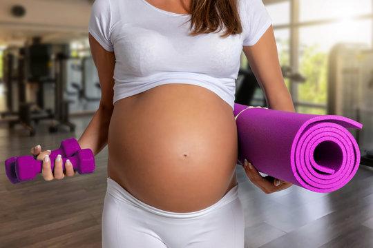 Schwangerschaft und Fitness Konzept: schwangere Frau mit Yoga Matte im Fitnessstudio