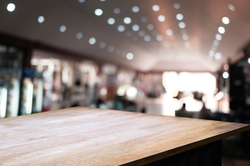 empty wooden table over blur restaurant / coffee shop cafe background