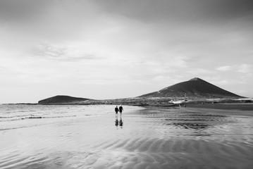 El Médano, Tenerife, Canary Islands, Spain - September 28, 2018: an older couple walking through El Médano beach, in south of Tenerife island